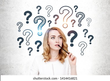 Thinking beautiful woman with red hair wearing smart casual clothes sitting near concrete wall with question marks drawn on it. Concept of looking for answer
