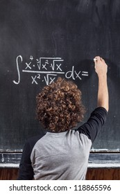 Thinking boy with blackboard solving equation, hard working student, funny portrait, written equation