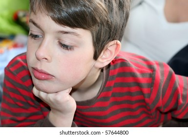 Thinking boy with hand under chin