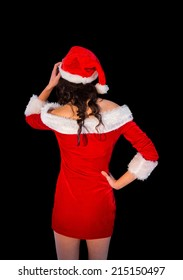 Thinking brunette in santa outfit posing with hand on hip on black background