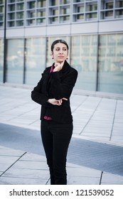 thinking business girl in front of modern building