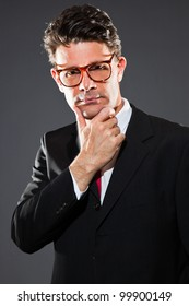 Thinking business man with dark grey suit and red tie isolated on dark background. Wearing retro glasses. Studio shot.
