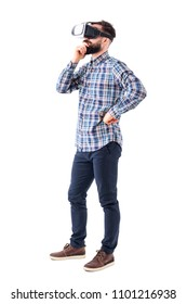 Thinking business man with hand on chin watching virtual reality glasses. Side view. Full body isolated on white background.