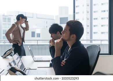 Thinking business persons in the office.