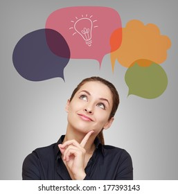 Thinking business woman with idea bulb in bubble on grey background