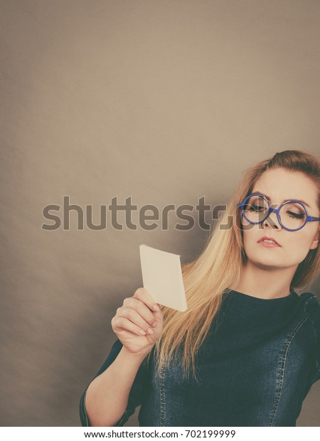 Thinking business woman wearing eyeglasses holding sticky note, looking at problem solution.