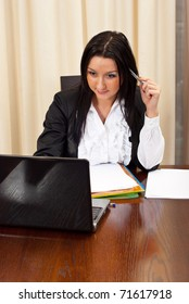 Thinking business woman working on laptop in office