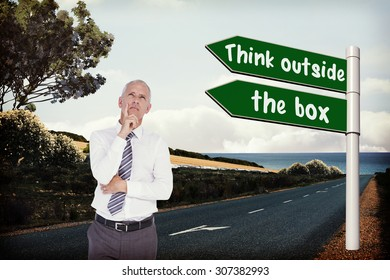 Thinking businessman against arrow signs on a road