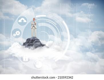 Thinking businessman against mountain peak through the clouds