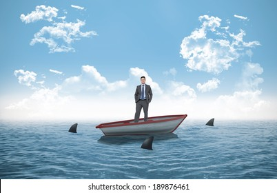 Thinking businessman against sharks circling small boat in the ocean