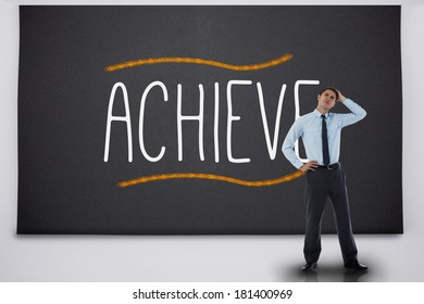 Thinking businessman against the word achieve