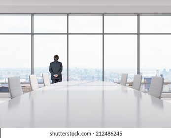 Thinking businessman in a Conference room. Modern office with windows and city view.