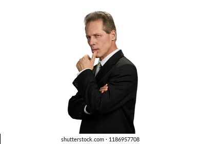 Thinking businessman with finger on chin. Serious middle-aged entrepreneur looking thoughtful, isolated on white background. Severe company leader.
