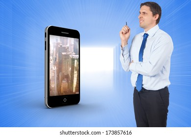 Thinking businessman holding pen against bright blue room