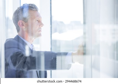 Thinking businessman in the office looking through the window