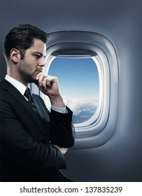thinking businessman standing in an airplane