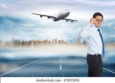 Thinking businessman tilting glasses against large city on the horizon