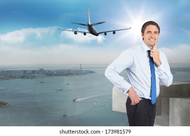 Thinking businessman touching his chin against balcony overlooking city