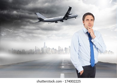 Thinking businessman touching his chin against open road