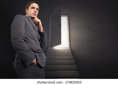 Thinking businessman touching his chin against steps leading to door showing light