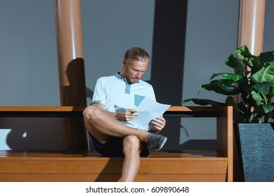 Thinking confident businessman with the papers. Horizontal indoors shot of a man sitting and looking into the papers.