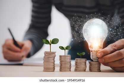 thinking and creative with Coins and light bulb concept,Close up light bulb and working on the desk, Creativity and innovation are keys to success.Concept of new idea and innovation with Brain.