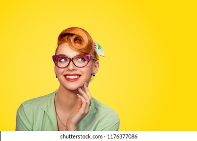 Thinking, daydreaming. Closeup portrait headshot thoughtful cute woman pinup girl in cat eye glasses looking up isolated on yellow background with copy space above head. Human face expression emotion.