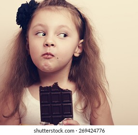 Thinking expression kid girl eating chocolate and looking fun. Closeup instagram portrait