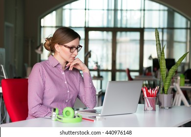 Thinking female Business Person smart casual Style Clothing working on Computer in modern Corporate Office Interior