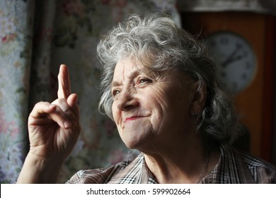 Thinking grandmother points a finger up