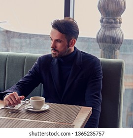 Thinking handsome bearded man sitting in cafe and drinking cup of coffee on the breakfast. Closeup portrait