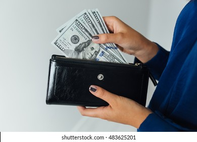 Thinking happy woman holding dollars and wallet in hands and want to spend money.