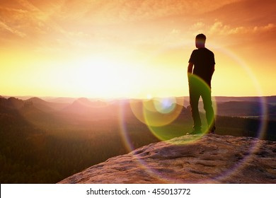 Thinking hiker in black on rocky peak. Wonderful daybreak. Ginger hair man in black at the end of sharp cliff above deep valley. Strong lens defect, reflection