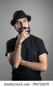 Thinking hipster wearing black t-shirt and hat stroking beard looking away.  Headshot portrait over gray studio background with vignette.