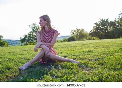 Thinking and lonley blonde wiman sitting on green grass