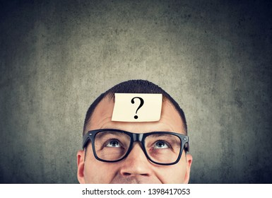 thinking man in glasses with question mark looking up on gray wall background