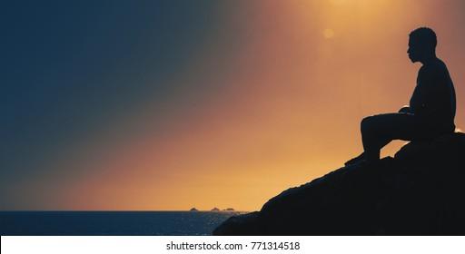 Thinking man on hill at sunset