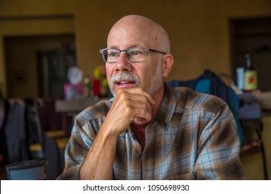 Thinking man portrait inside plaid Caucasian glasses bald beard white gray older smart intelligent