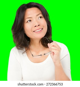 Thinking mature asian woman holding glasses eyewear looking up to the side at copy space. Asian Chinese mature woman isolated cutout on green chroma key background.