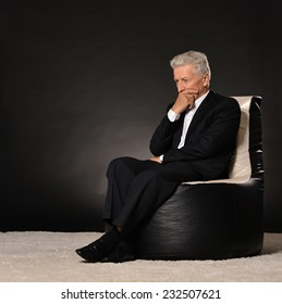 Thinking mature businessman sitting in chair on black background