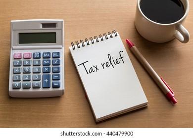 Denken Sie an Steuererleichterung, Personalfinanzkonzeptuelle - Handschrift auf Notizblock mit Tasse Kaffee und Taschenrechner