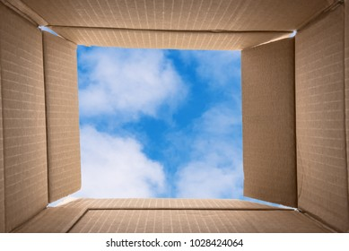 Thinking Outside the Box. Conceptual Image about Creative thinking: photo of the inside of an Open Cardboard Box with a Blue Sky with Clouds in Background