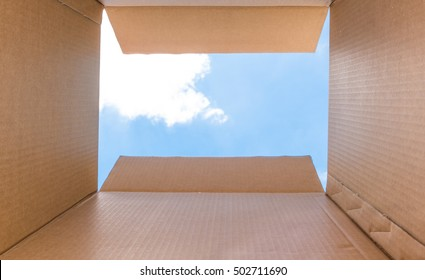 """Thinking Outside the Box"" for Create New Ideas and Innovation concept. Inside a cardboard with clear sky and cloud for Background"