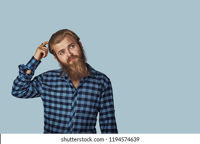 Thinking perplexed man looking up. Thoughtful guy scratching head solving a problem. Hipster male with beard in blue plaid checkered shirt. Isolated on blue studio Background. Negative face expression