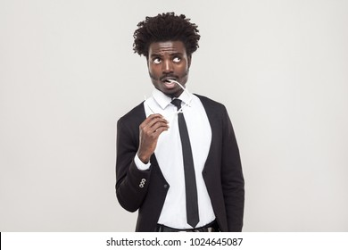 Thinking, pleased people. African businessman pondering and looking up. Studio shot, gray background