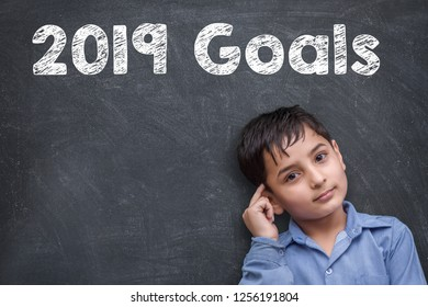 Thinking Position of A Young Asian kid boy while standing against blackboard with chalk drawing of new year 2019 goals