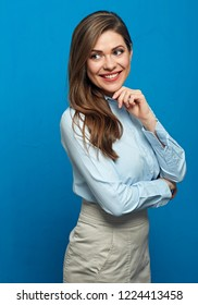 Thinking positive business woman standing in front of blue wall. Studio isolated portrait.
