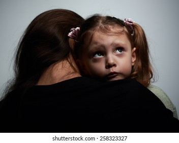 Thinking sad daughter embracing her mother and looking up on dark background