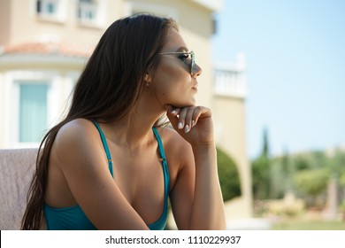thinking and sad woman sitting by the swimming pool