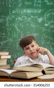 Thinking schoolboy sitting at desk with book